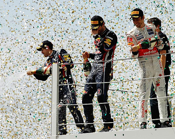 Red Bull's Mark Webber (centre) celebrates on the podium with teammate Sebastian Vettel and third placed Jenson Button (right) of McLaren