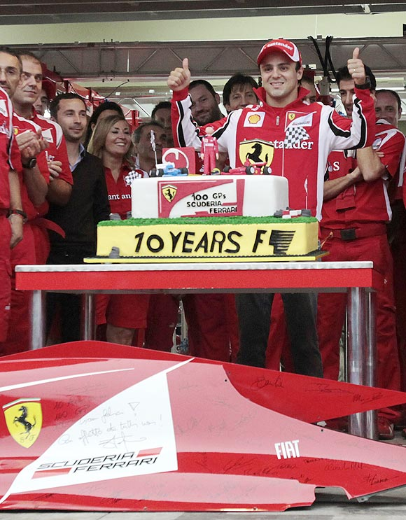 Felipe Massa poses with a cake to celebrate his 100th Formula One race for Ferrari