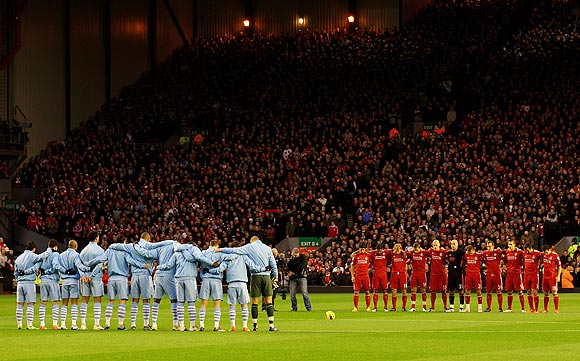 The Liverpool and Manchester City players observe a minute's silence in memory of Wales manager, the late Gary Speed