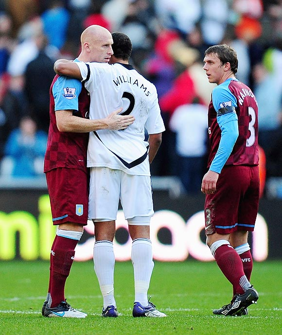 Ashley Williams of Swansea shakes hands with fellow Wales international player and Aston Villa's James Collins