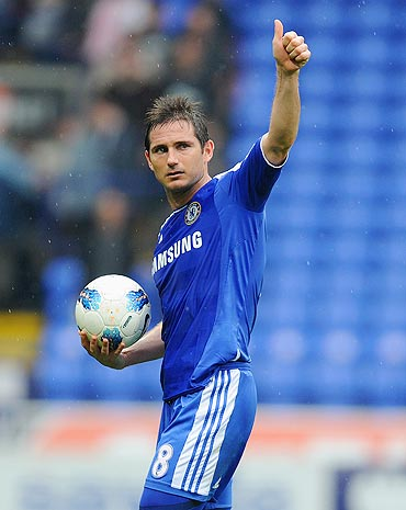Frank Lampard of Chelsea celebrates with the match ball after scoring a hat-trick during the Barclays Premier League match against Bolton Wanderers on Sunday