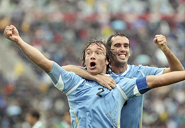 Uruguay's Diego Lugano (left) celebrates with team-mate Diego Godin after scoring against Bolivia during their World Cup qualifying football match