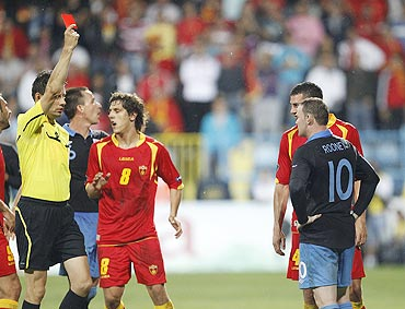 Referee Wolfgang Stark (left) sends off England's Wayne Rooney (right) during their Euro 2012 Group G qualifying match against Montenegro