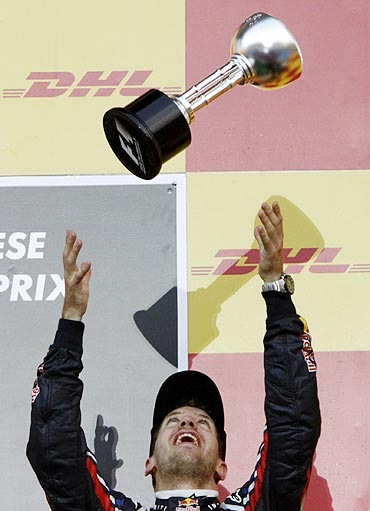 Sebastian Vettel tosses his trophy in the air as he celebrates winning the world championship