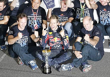 Red Bull's Sebastian Vettel (centre) celebrates with crew members after winning the championship title following the Japan GP on Sunday