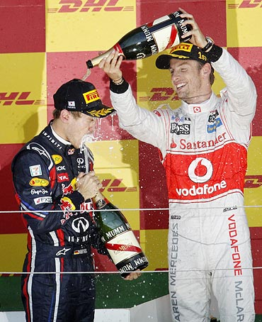 McLaren's Jenson Button (right) pours champagne over Red Bull's Sebastian Vettel as they celebrate on the podium after the Japanese GP
