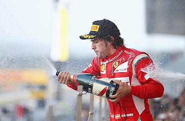 Ferrari's Fernando Alonso celebrates with champagne after the Japan GP