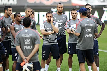 French soccer players listen to head coach Laurent Blanc (right) during their official training