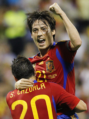 Spain's David Silva celebrates with teammate Santi Cazorla after scoring against Scotland during their Euro 2012 qualifying Group I soccer match at the Perez Rico Stadium in Alicante