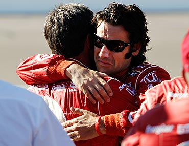 Dario Franchitti, driver of the 10 Target Chip Ganassi Racing Dallara Honda hugs a crew member after the death of Dan Wheldon
