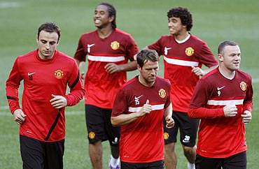 Manchester United players run to warm up at the start of their training session