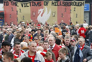 Liverpool Football Club supporters queue to enter a memorial service at Liverpool's Anfield stadium to mark the 20th anniversary of the Hillsborough disaster