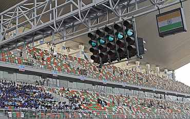 An Indian national flag flashes with a green signal as spectators watch at the Buddh International Circuit