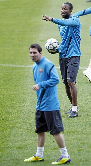 Barcelona's Lionel Messi and Seydou Keita attend a training session at Camp Nou stadium in Barcelona