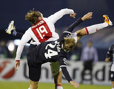 Dmitri Bulykin (left) of Ajax Amsterdam challenges Domagoj Vida of Dinamo Zagreb