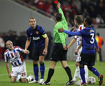 Nemanja Vidic (2nd from left) is booked by the referee