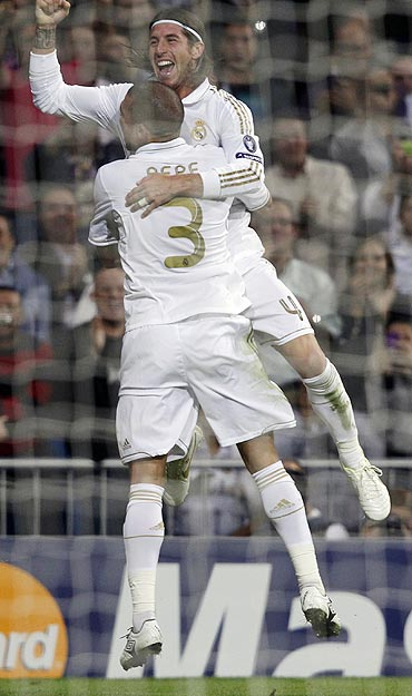 Real Madrid's Sergio Ramos celebrates with teammate Pepe after scoring against Olympique Lyon