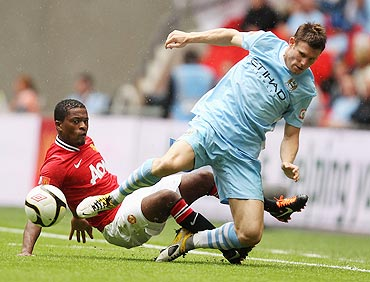 Patrice Evra of Manchester United tackles James Milner of Manchester City