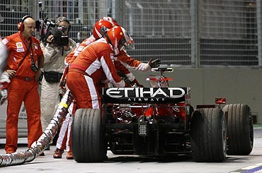 Ferrari pit crew gesture while attempting to remove a fuel hose from the car of Ferrari Formula One driver Felipe Massa