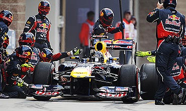 Red Bull's crew members change the tyres during a pitstop by Sebastian Vettel