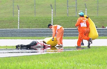 Honda MotoGP's Marco Simoncelli of Italy lies on the ground after a crash during the Malaysian Grand Prix