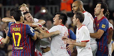 Cesc Fabregas is grabbed by the throat (left) as Barcelona and Sevilla players argue after a penalty during their La Liga match at Camp Nou stadium in Barcelona on Saturday