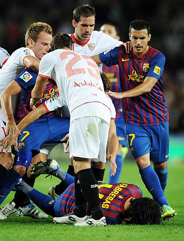 Cesc Fabreas lays on the pitch after a scuffle with Sevilla players