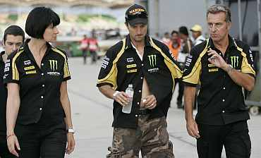 Yamaha's Colin Edwards listens to his crew as he leaves the medical centre after a crash with Honda MotoGP rider Marco Simoncelli