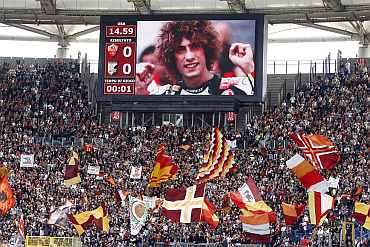 A picture showing the italian MotoGP rider Marco Simoncelli is seen on a giant screen before the Italian Serie A soccer match in Rome