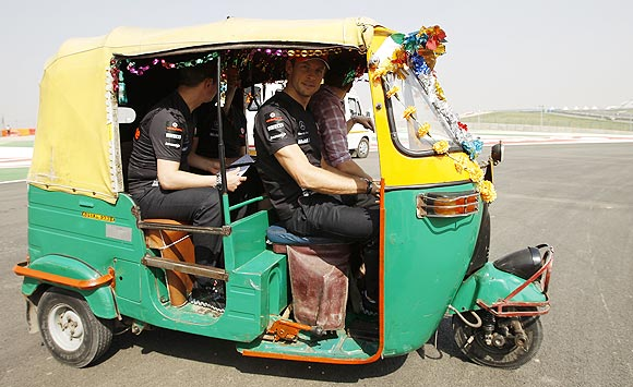 McLaren's Jenson Button drives an auto rickshaw at the Buddh International Circuit in Greater Noida on Thursday