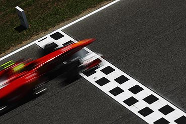 Felipe Massa of Ferrari drives past the DRS zone indication board