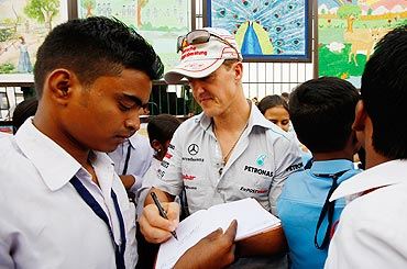 Michael Schumacher signs autographs for fans during previews to the Indian Formula One Grand Prix