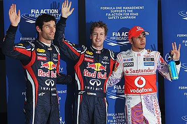 Red Bull's Pole sitter Sebastian Vettel (centre) celebrates with teammate and second placed Mark Webber (left) and third placed Lewis Hamilton (right) of McLaren after qualifying