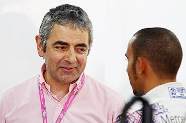 Actor Rowan Atkinson (left) talks with McLaren's Lewis Hamilton (right) in the McLaren garage on Saturday