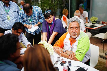 Force India's chairman Vijay Mallya is interviewed by the media following qualifying at the Indian Grand Prix on Saturday
