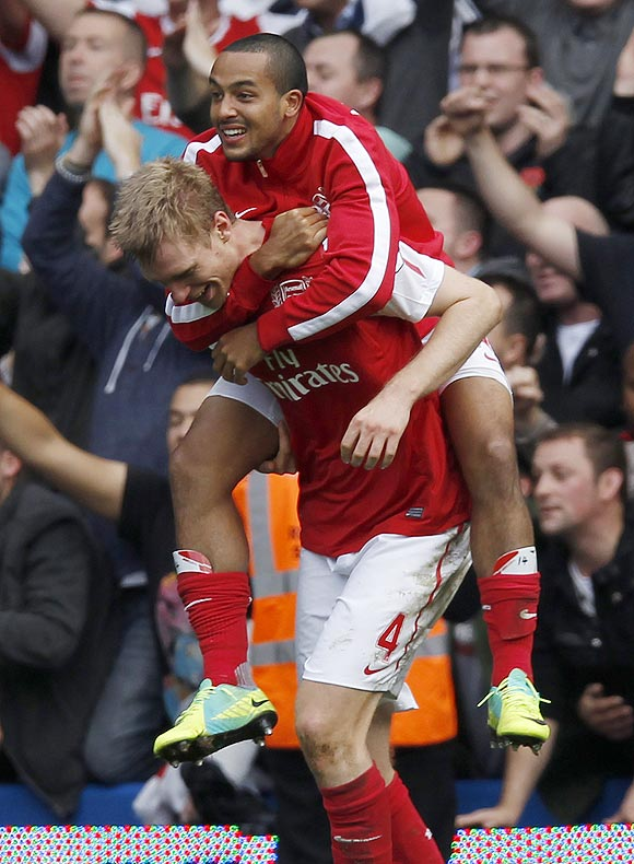 Arsenal's Theo Walcott (top) and Per Mertesacker celebrate after beating Chelsea