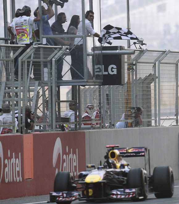 Sachin Tendulkar waves the chequered flag for Red Bull Formula One driver Vettel as he crosses the finish line