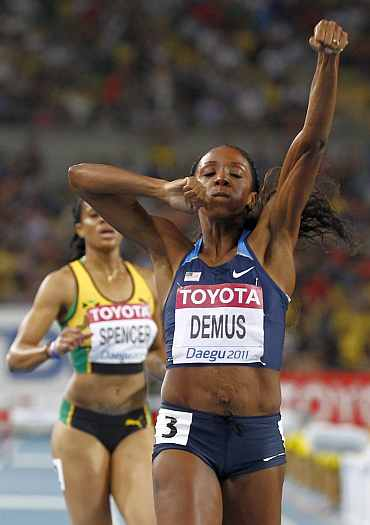 Lashinda Demus of the U.S. celebrates next to Spencer of Jamaica after winning the women's 400 metres hurdles final