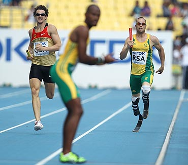 South Africa's Oscar Pistorius runs towards teammate Ofentse Mogawane during the men's 4x400 metres relay heats on Thursday