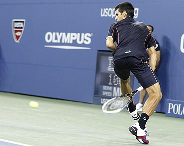 Novak Djokovic returns the ball between his legs against Carlos Berlocq
