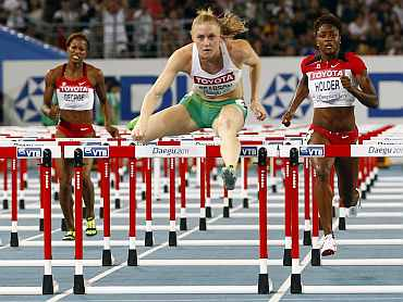 Sally Pearson of Australia clears a hurdle next to Holder of Canada and George of Canada to win the women's 100 metres hurdles