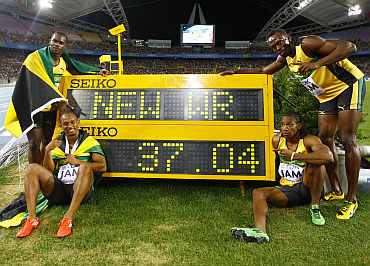 Usain Bolt stands next to the record