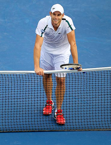 Andy Roddick celebrates at the net after defeating Julien Benneteau