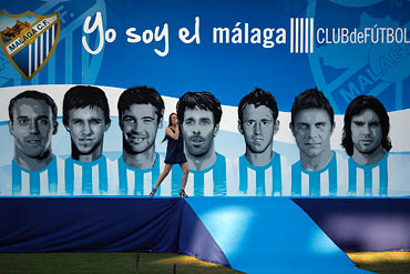 Spanish singer Maria Villalon sings in front of pictures of Malaga's players (L-R) Joris Mathijsen, Diego Buonanotte, Jeremy Toulalan, Ruud van Nistelrooy, Ignacio Monreal, Joaquin