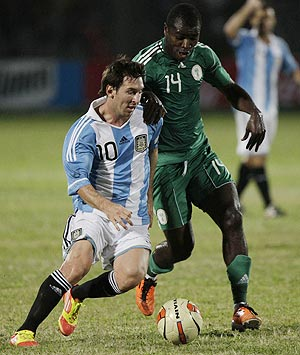 Argentina's Lionel Messi fights for the ball with Nigeria's Ogude Fegor (right) during their international friendly in Dhaka on Tuesday