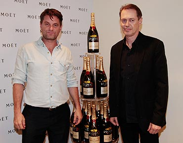 Shea Whigham and Steve Buscemi smile before signing a Moet  and Chandon Champagne bottle