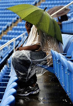 A fan sits down with umbrella as rain falls to delay matches on Tuesday