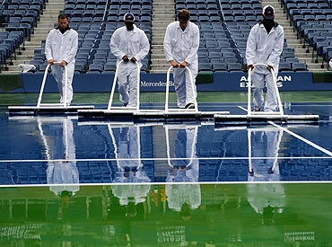 Workers dry the court at Arthur Ashe Stadium on Wednesday