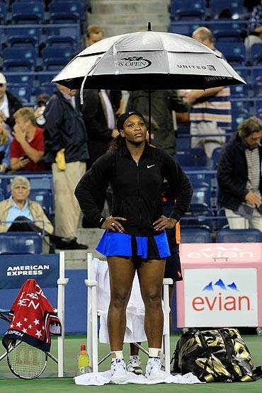 Serena Williams sits under an umbrella during a rain delay prior to her scheduled match against Anastasia Pavlyuchenkova
