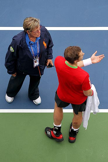 Andy Murray (right) talks with WTA tour director Pam Whytcross following delay in play against Donald Young